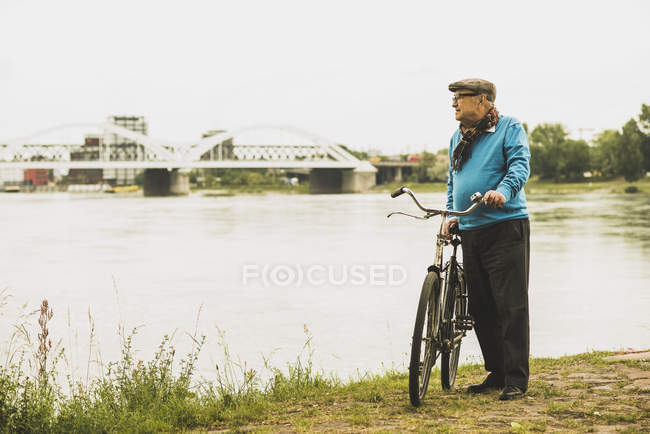 Senior man standing with his bicycle at water's edge — Stock Photo