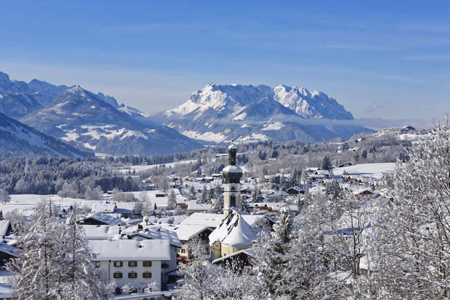 Germania, Baviera, Alta Baviera, Chiemgau, Vista su Reit im Winkl in inverno, montagne Kaiser sullo sfondo innevate — Foto stock