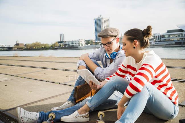 Jovem e mulher sentados em trilhas usando tablet digital — Fotografia de Stock
