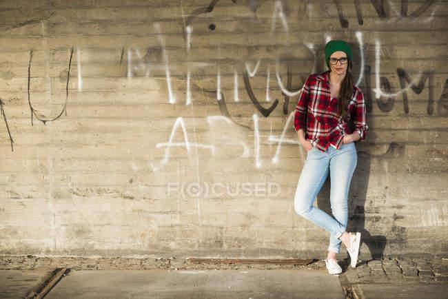 Молодая женщина с клетчатой рубашке и мохнатый шляпу, опираясь на граффити стены — стоковое фото