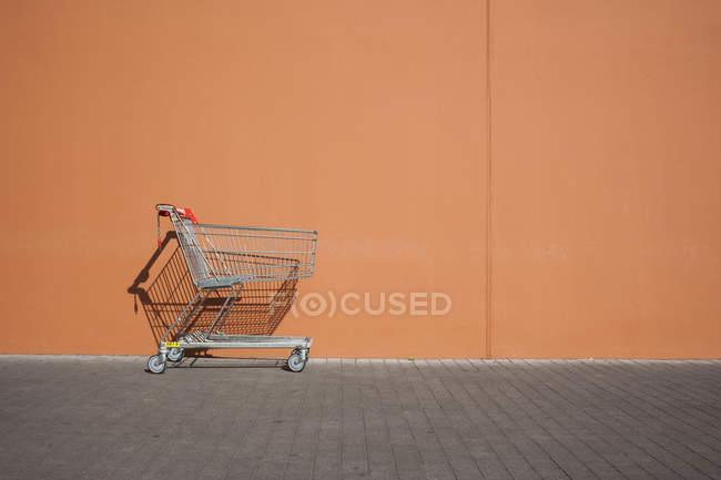 Empty parked shopping cart near wall — Stock Photo