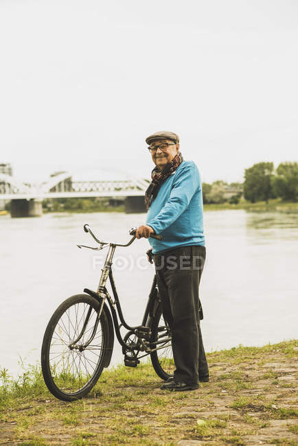 Portrait of smiling senior man standing with his bicycle at water's edge — Stock Photo