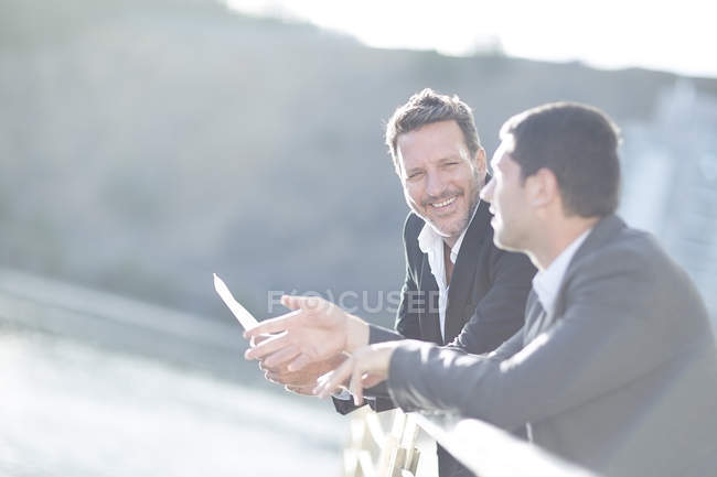 Smiling Businessmen leaning at railing and talking — Stock Photo