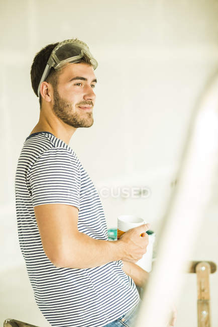 Young man having a coffee break from renovating — Stock Photo