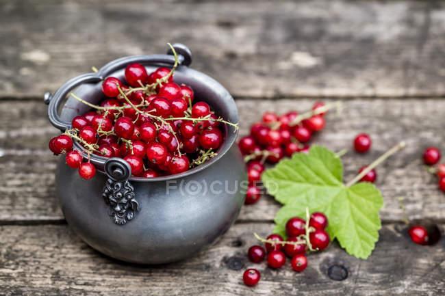 Grosellas rojas frescas en cuenco de zinc sobre madera oscura con hoja - foto de stock