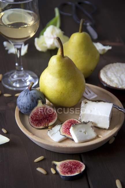 Различные сыры, вино, груши, инжир и кедровыми орешками — стоковое фото