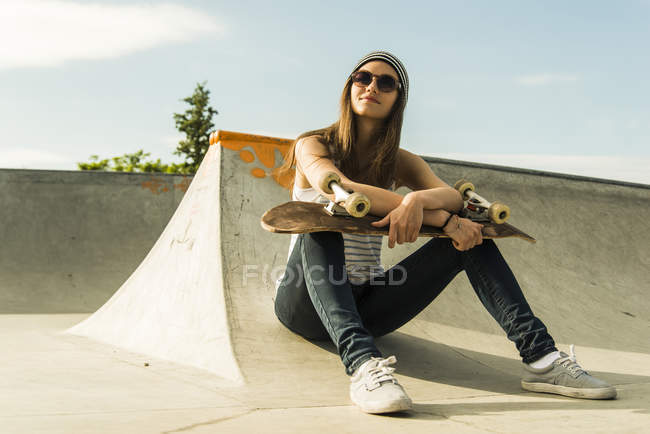 Portrait of young skate boarder wearing sunglasses sitting in a skatepark — Stock Photo