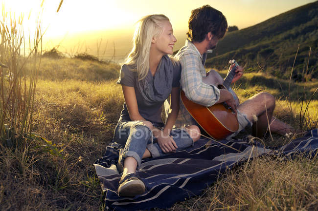 Young couple with guitar on blanket in meadow — Stock Photo