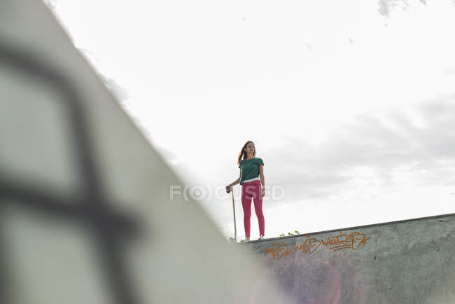 Jeune skate boarder debout sur un mur regardant loin — Photo de stock