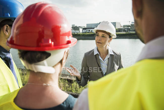 Businesswoman talking to people with safety helmets at riverside — Stock Photo