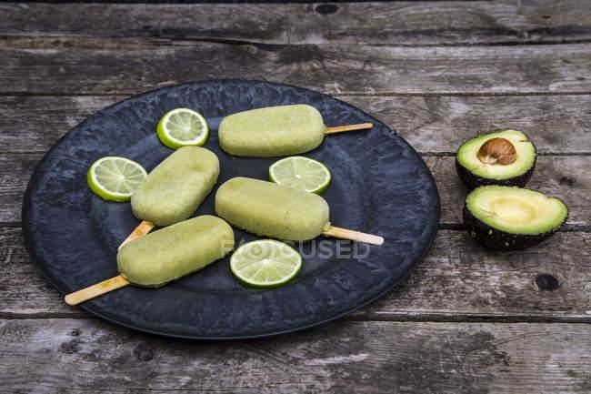 Primo piano del piatto di avocado ghiaccioli e fette di lime — Foto stock