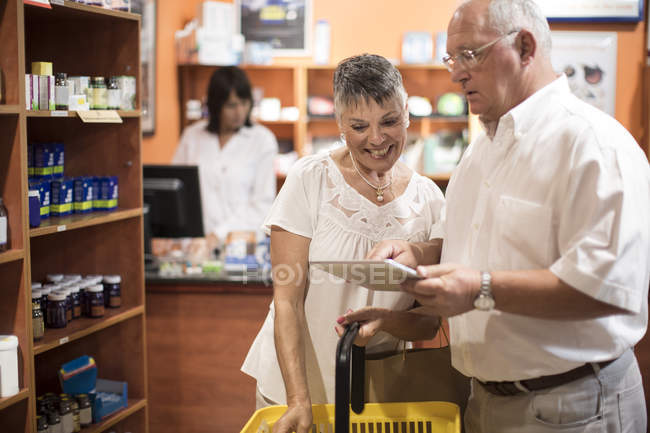 Senior couple using digital tablet in health shop — Stock Photo