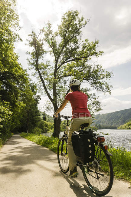 Germany, Cochem, woman riding bycicle along riverside of Moselle — Stock Photo