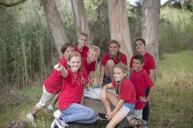 Kids and woman on field trip exploring nature — Stock Photo