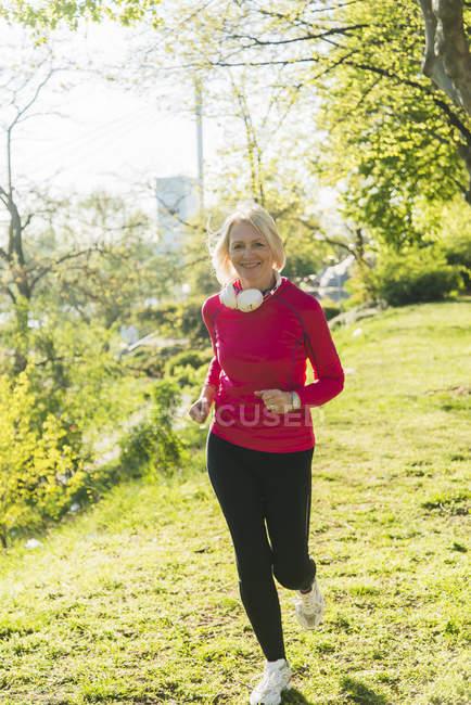 Donna matura fare jogging nel parco — Foto stock