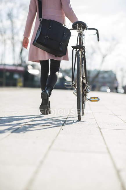 Jovem mulher com bicicleta na cidade — Fotografia de Stock
