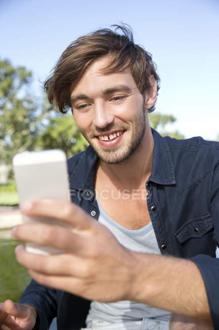 Souriant jeune homme dans le parc prendre un selfie — Photo de stock