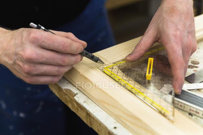 Изготовитель рамок в мастерской маркирует деревянную раму — стоковое фото
