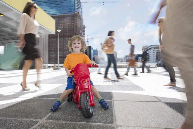 Хлопчик їзда пластикові триколісний велосипед між натовп людей в місті — стокове фото