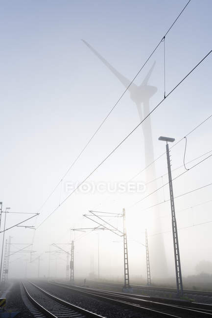 Germany, Hamburg, wind turbine next to railway track in early morning fog — Stock Photo