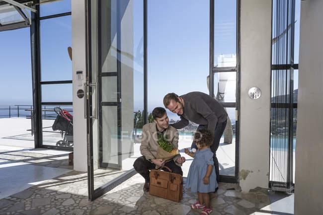 Pareja gay y niño en la puerta principal con comestibles - foto de stock