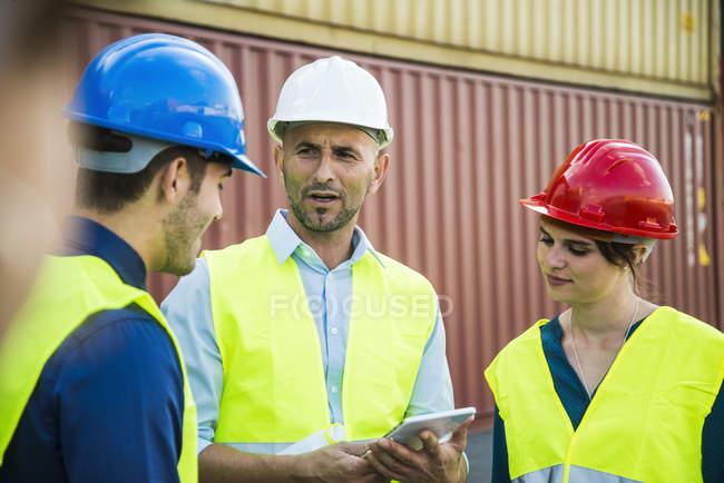 Femme et deux hommes avec des casques de sécurité parlant au port de conteneurs — Photo de stock