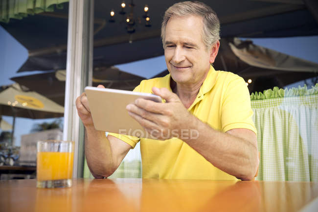 Portrait of senior man using digital tablet in a cafe — Stock Photo