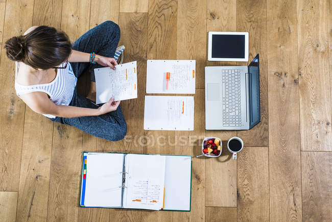 Student sitzt auf Holzboden, umgeben von Papieren, Laptop, digitalem Tablet, Aktenordner, Kaffee und Obstschale — Stockfoto