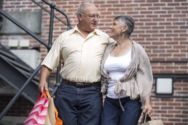 Счастливая пожилая пара с сумками — стоковое фото