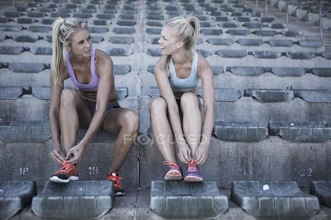 Две спортсменки сидят на трибуне стадиона, завязывая ботинки — стоковое фото