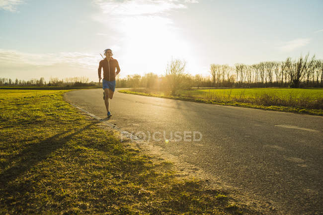 Молодой человек бегает по сельской дороге — стоковое фото
