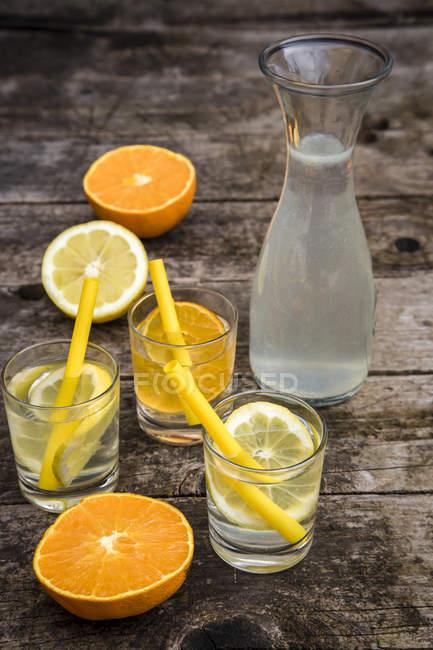 Glasses of homemade lemonade and orangeade on table — Stock Photo