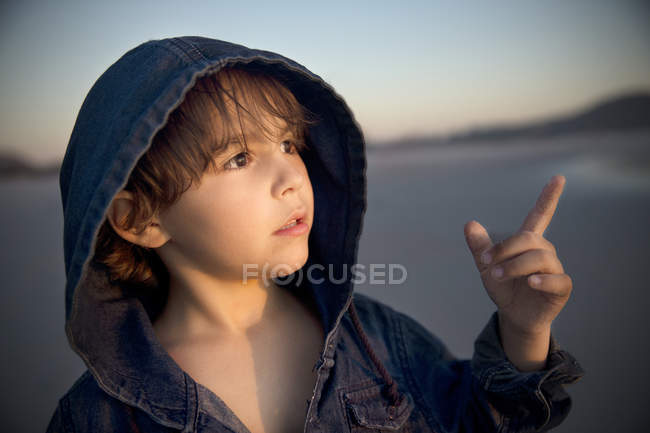 Boy on beach pointing his finger — Stock Photo