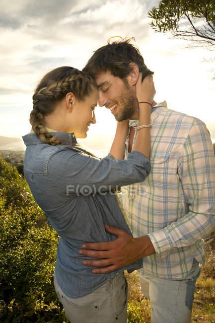 Tierna pareja joven en la costa al atardecer - foto de stock