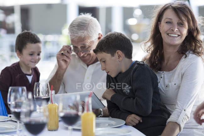 Abuelo y nietos con tableta digital en celebración de la familia - foto de stock