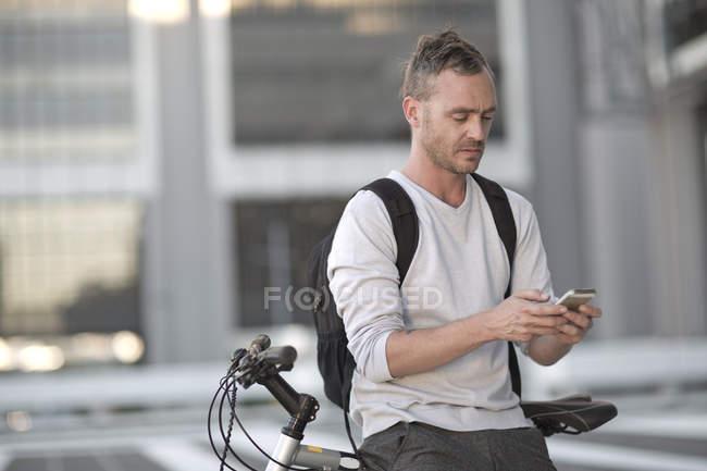 Blone man on bicycle using smart phone — Stock Photo