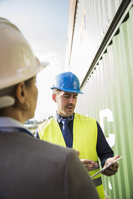Businesswoman and man with safety helmets and digital tablet at container port — Stock Photo