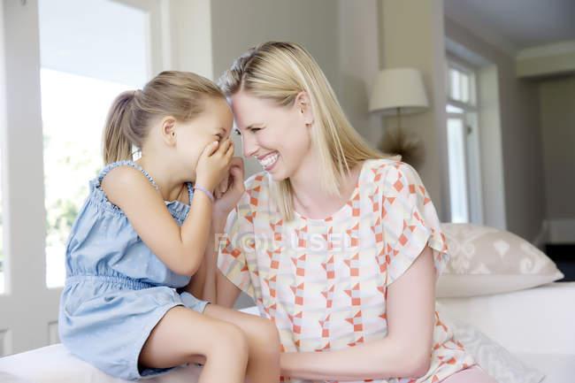 Madre e hija sentadas en el sofá, riéndose - foto de stock