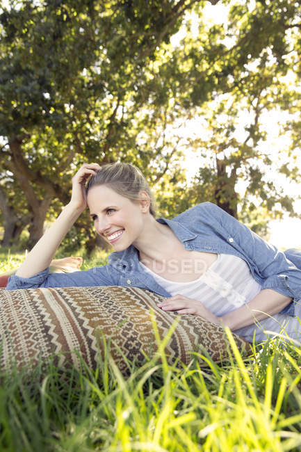 Smiling woman lying on meadow — Stock Photo