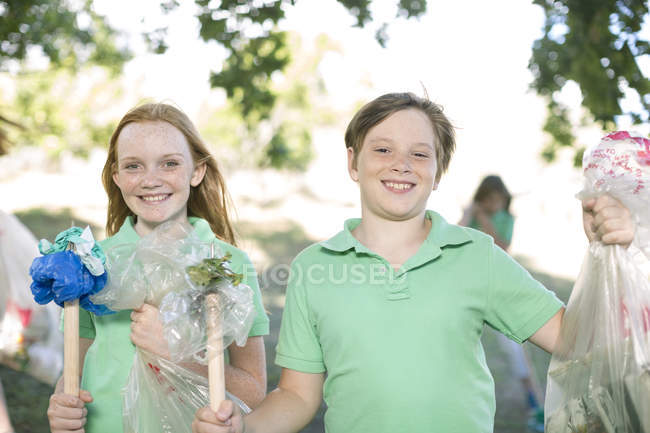 Portrait of smiling boy and girl showing picked up garbage — Stock Photo