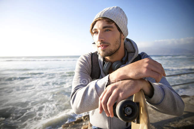 Young man with longboard at the coast — Stock Photo