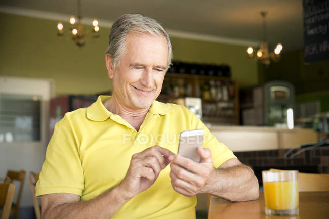 Portrait of senior man using smartphone in a cafe — Stock Photo
