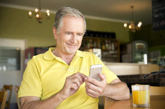 Ritratto dell'uomo maggiore utilizzando smartphone in un caffè — Foto stock