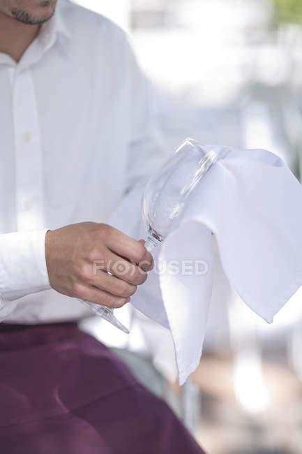 Официант чистит бокал вина тканью — стоковое фото