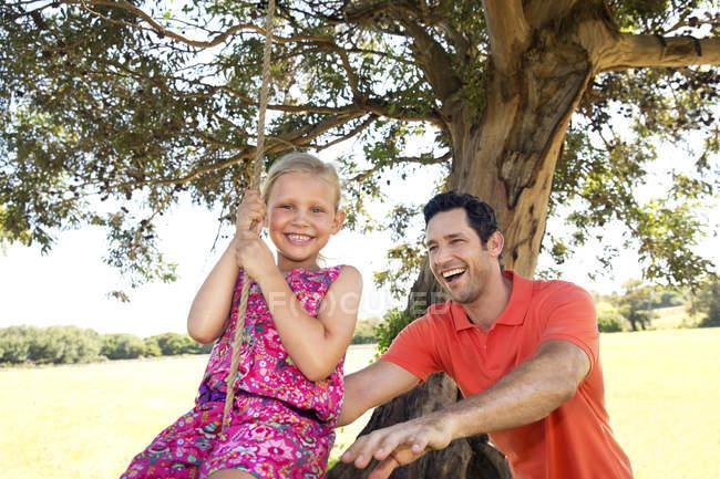 Отец играет с дочерью на качелях — стоковое фото