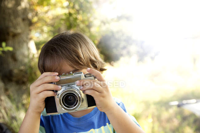 Boy with analog camera taking a picture outdoors — Stock Photo