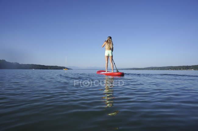 Молода жінка, стоячи на встати весло ради в Штарнберг, задній вид — стокове фото