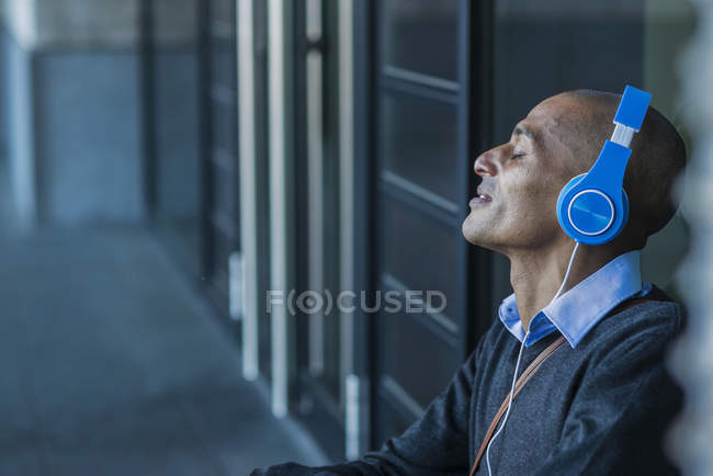 Man wearing headphones leaning against glass front — Stock Photo