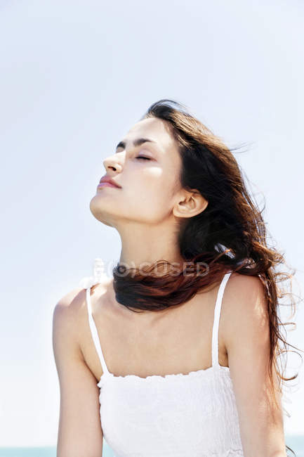 Brunette young woman with closed eyes enjoying sunshine — Stock Photo