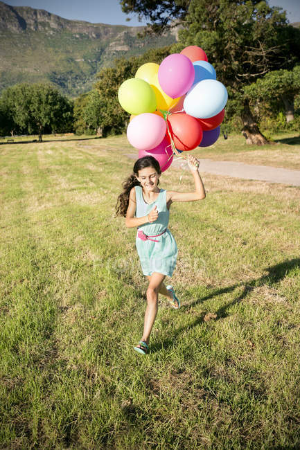 Happy girl running with balloons on meadow — Stock Photo